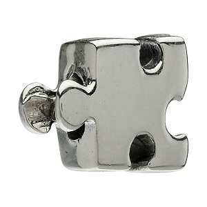 Silver charm in shape of a puzzle piece