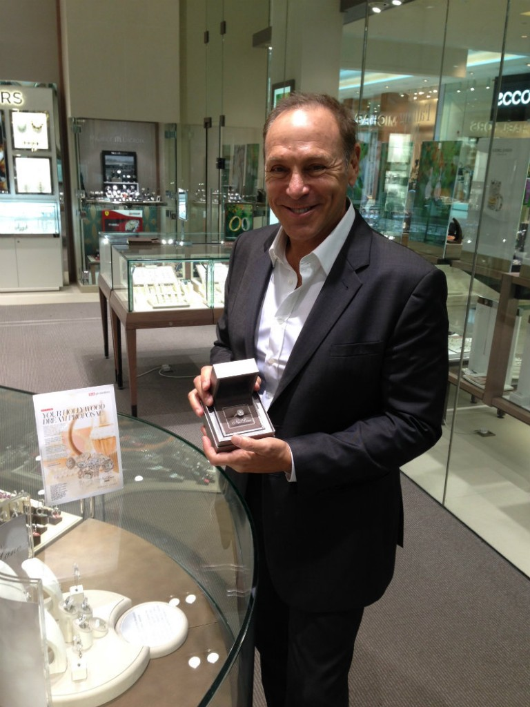 Neil Lane in an Ernest Jones store showing a ring from his collection