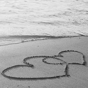 Two hearts drawn in the sand on a beach