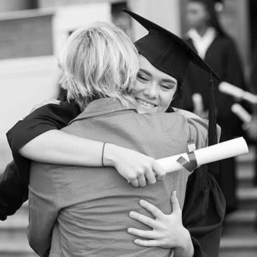 Graduate holding degree scroll and hugging mother