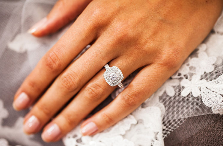 A hand wearing a Tolkowsky diamond engagement ring