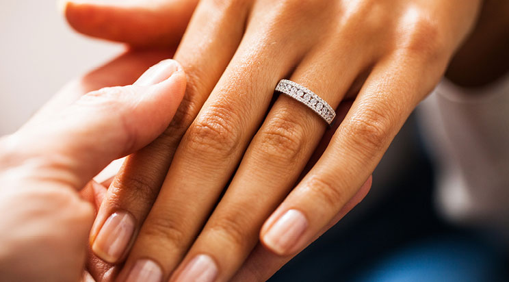 A hand wearing a Tolkowsky diamond wedding band